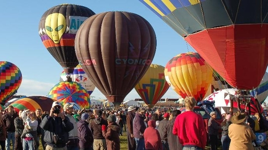 FILE - In this Oct. 8, 2011 file photo, hot air balloons are shown at the Albuquerque International Balloon Fiesta before take off. The world's largest gathering of hot air balloons is getting ready to kick off and organizers want to be clear: No drones allowed. Hundreds of balloon pilots will be lifting off around dawn Saturday, Oct. 4, 2014, marking the first mass accession of the nine-day Albuquerque International Balloon Fiesta. (AP Photo/Russell Contreras,File)