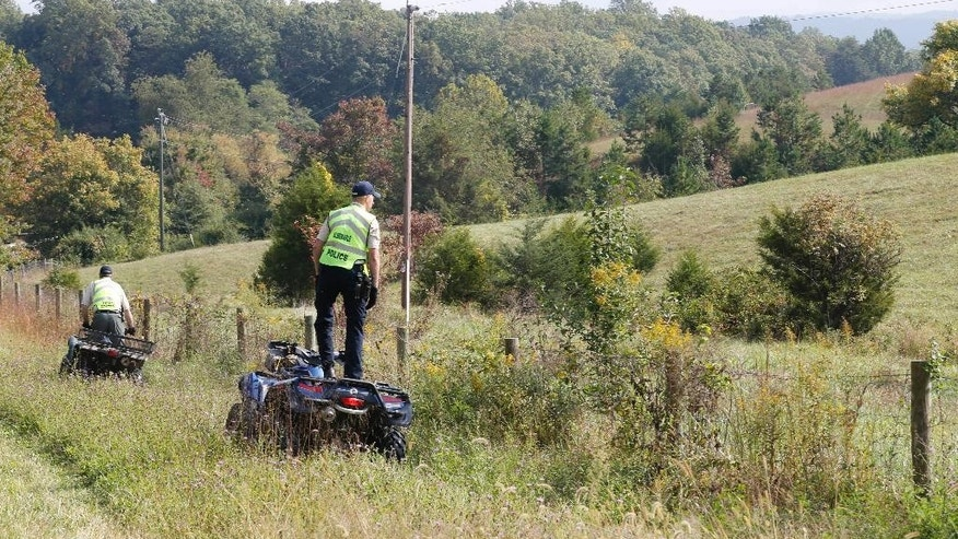 Police on ATV's search the fence line along a highway for any sign of missing University of Virginia student Hannah Graham in Keswick, Va., Thursday, Oct. 2, 2014.  Jesse Leroy Matthew Jr., charged with abducting Graham, didn't appear in court Thursday morning for a bond hearing on reckless driving charges.   (AP Photo/Steve Helber)