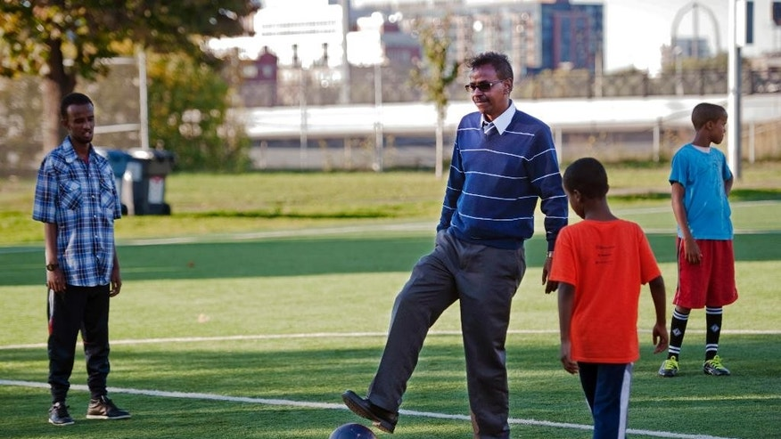 In this Monday, Sept. 22, 2014 photo, Abdirizak Bihi, right, executive director of the Somali Education and Social Advocacy Center, spends time with kids playing soccer at Currie Park in Minneapolis, near a large Somali community in the Cedar Riverside neighborhood. While Bihi strolls through the neighborhood parks, he is on the lookout for anyone who might be trying to recruit the city's young Somalis to join jihad in Syria. (AP Photo/Craig Lassig)
