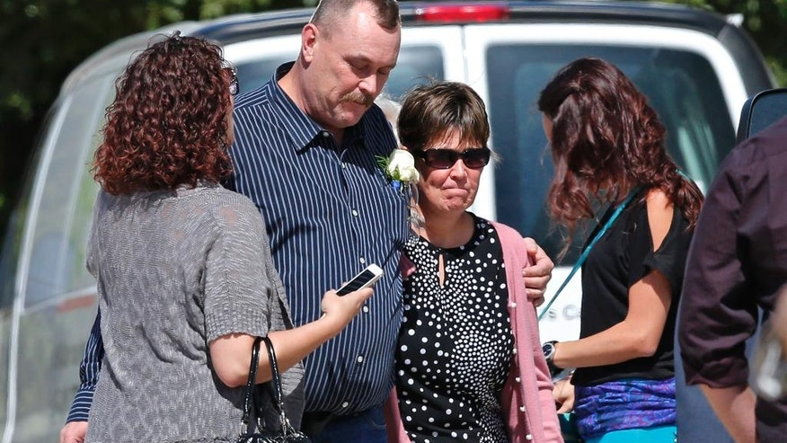 K.C. Hufford, second from left, the widower of Colleen Hufford, stands with other mourners before the start of the funeral for Colleen Hufford at Southgate Baptist Church in Moore, Okla., Friday, Oct. 3, 2014. Colleen Hufford was killed in a workplace violence incident on Sept. 25th. (AP Photo/Sue Ogrocki)
