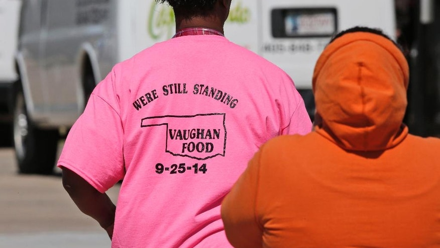 "A woman wearing a shirt that reads ""Were Still Standing, Vaughan Food, 9-25-2014"", arrives for the funeral of Colleen Hufford at Southgate Baptist Church in Moore, Okla., Friday, Oct. 3, 2014. Hufford was killed in a workplace violence incident at Vaughan Food on Sept. 25th. (AP Photo/Sue Ogrocki)"