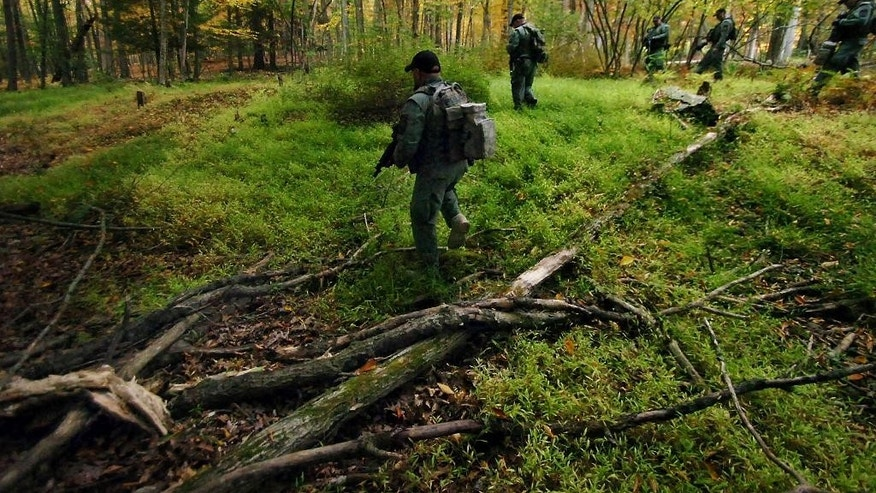 Members of the Scranton, Pa., Police Special Operations Group, search the woods, Thursday, Oct. 2, 2014, in Barrett Township near Canadensis, Pa., for suspected killer Eric Frein. A massive manhunt has been underway for 31-year-old Frein in the rugged terrain of the Pocono Mountains since Sept. 12. The self-taught survivalist is charged with killing Cpl. Bryon Dickson and seriously wounding Trooper Alex Douglass outside their barracks in Blooming Grove. (AP Photo/Scranton Times & Tribune, Butch Comegys)  WILKES BARRE TIMES-LEADER OUT; MANDATORY CREDIT