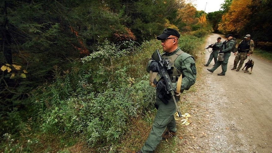 A member of the Scranton, Pa., Police Special Operations Group, prepares to ender the woods, Thursday, Oct. 2, 2014, in Barrett Township near Canadensis, Pa., to search for suspected killer Eric Frein. A massive manhunt has been underway for 31-year-old Frein in the rugged terrain of the Pocono Mountains since Sept. 12. The self-taught survivalist is charged with killing Cpl. Bryon Dickson and seriously wounding Trooper Alex Douglass outside their barracks in Blooming Grove. (AP Photo/Scranton Times & Tribune, Butch Comegys)  WILKES BARRE TIMES-LEADER OUT; MANDATORY CREDIT