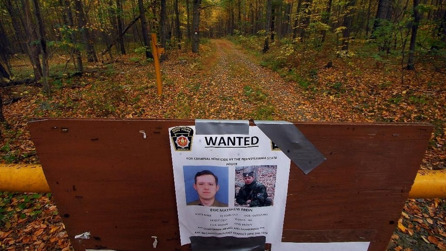 A wanted poster of suspected killer Eric Frein is posted at an entrance to a trail in the woods, Thursday, Oct. 2, 2014, in Barrett Township near Canadensis, Pa. A massive manhunt has been underway for 31-year-old Frein in the rugged terrain of the Pocono Mountains since Sept. 12. The self-taught survivalist is charged with killing Cpl. Bryon Dickson and seriously wounding Trooper Alex Douglass outside their barracks in Blooming Grove. (AP Photo/Scranton Times & Tribune, Butch Comegys)  WILKES BARRE TIMES-LEADER OUT; MANDATORY CREDIT