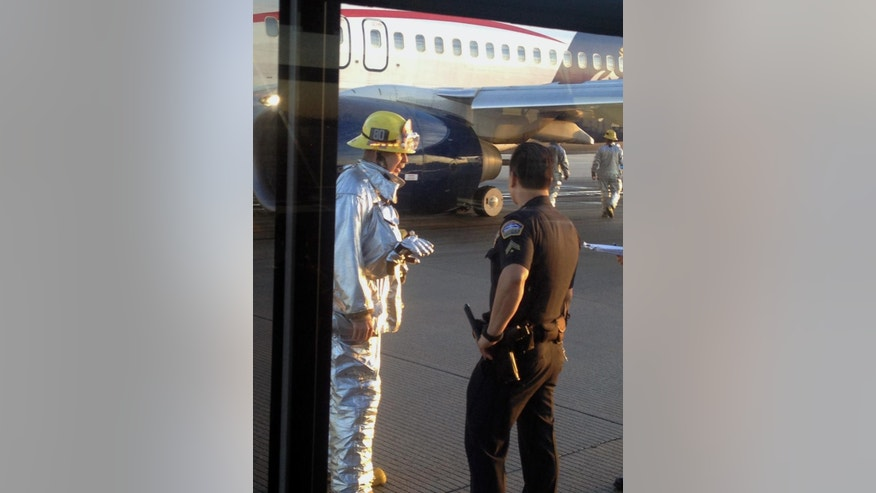 In this photo provided by Sara Seligman authorities work the scene at Los Angeles International Airport after a Mexico City-bound Aeromexico jet hit its brakes after the left landing gear collapsed while it was preparing to depart from a runway Saturday, Oct. 4, 2014, in Los Angeles. No injuries were reported. (AP Photo/Sara Seligman) MANDATORY CREDIT