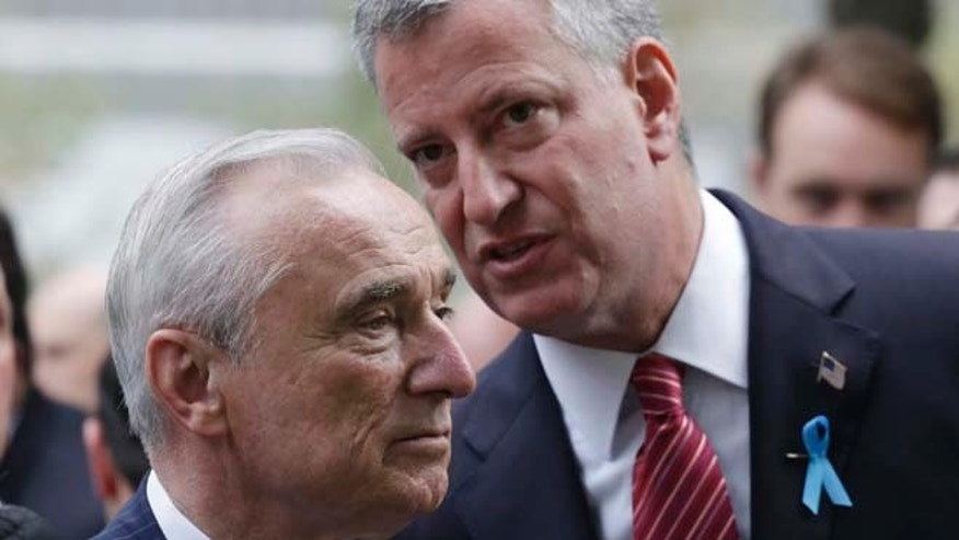 FILE 2014: New York City Police Commissioner Bill Bratton, left, and Mayor Bill de Blasio talk during memorial observances at the site of the World Trade Center in New York.