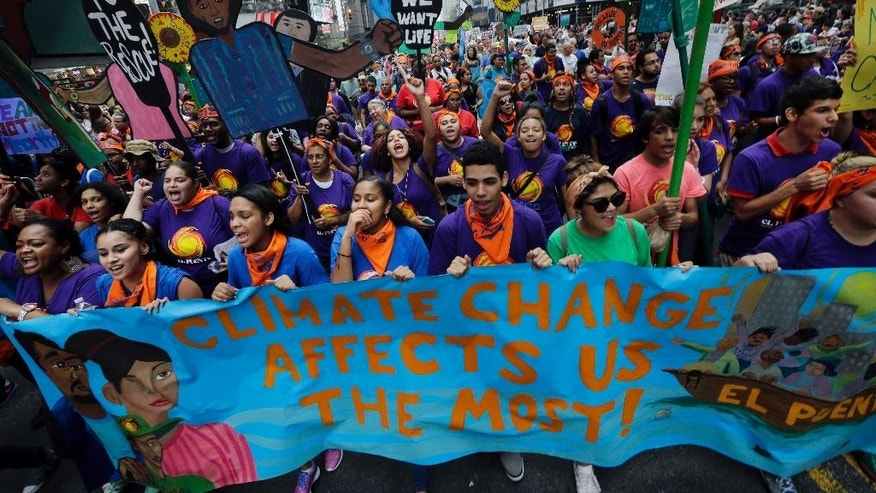 FILE - In the Sept. 21, 2014 file photo thousands of young people fill the streets of Manhattan, New York, carrying banners and calling on policymakers to take action on climate change. According to a new Associated Press-GfK poll, conducted September 25-29, 2014, Americans lack confidence that their government can keep them safe from threats to their safety and economic security. More than half of those polled don't think the U.S. government can do much to effectively minimize the threat posed by climate change, mass shootings, racial tensions, economic uncertainty on Wall Street and an unstable job market. (AP Photo/Mel Evans, File)