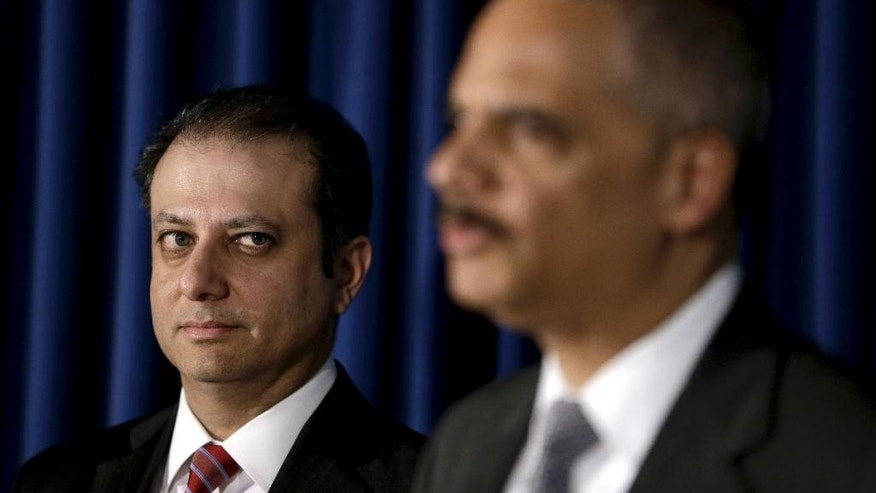 FILE - In this April 1, 2014 file photo, U.S. Attorney for the Southern District of New York Preet Bharara, left, looks on as U.S. Attorney General Eric Holder speaks during a news conference in New York. Bharara is considered to be among fewer than 10 top candidates to replace Holder when he steps down as Attorney General. (AP Photo/Seth Wenig, File)