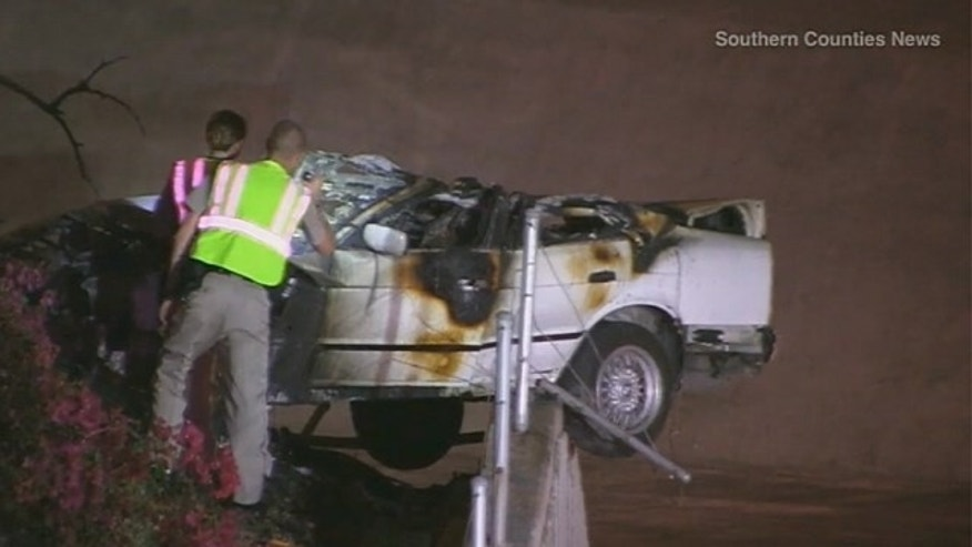 October 4, 2014: Workers remove a car from the scene of a crash on the Santa Ana Freeway in Irvine, Calif. that killed 5 teenagers. (MyFoxLA.com)