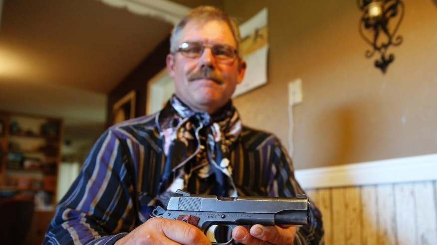 Kim Clark, senior investigator for the Wyoming Livestock Board, poses for a picture with his Colt .45 semi-automatic pistol on Oct. 2, 2014 in Cokeville, Wyo. Clark's law enforcement unit which investigates cattle thefts and other industry related crimes were given seven .45-caliber handguns from a military surplus program roughly three years ago. (AP Photo/George Frey)