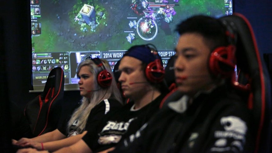 "In this Sept. 23, 2014 photo, Robert Morris University Illinois freshmen, from left, Sondra Burrows, Brian Rodonis and Alex Chapman practice playing the video game ""League of Legends"" with their collegiate teammates at their on-campus training facility in Chicago. The small private university is offering hefty scholarships for players of ""League of Legends,"" which has become one of the most popular games for organized team competitions nationwide. (AP Photo/M. Spencer Green)"