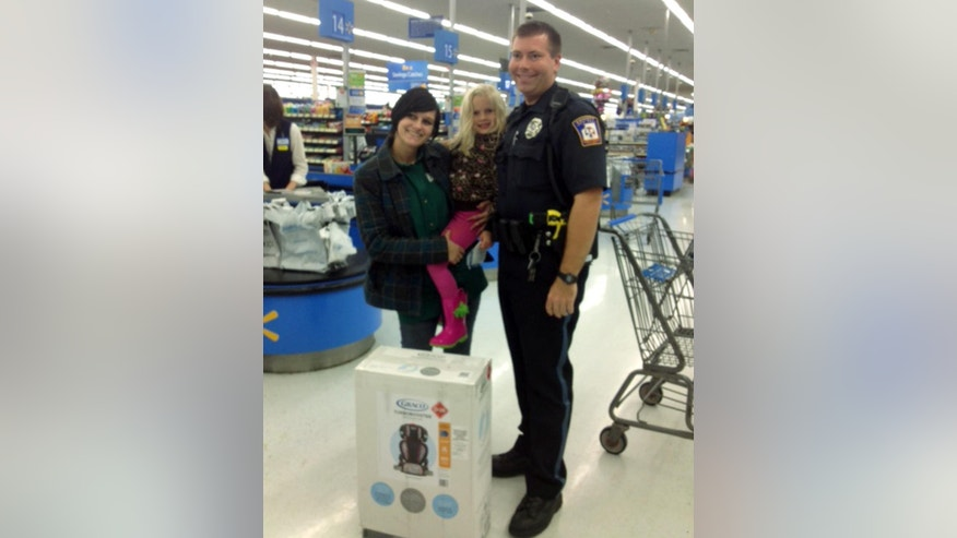 This photo provided by Walmart shows Emmett Township, Mich., Department of Public Safety Officer Ben Hall, right, with Alexis DeLorenzo, her daughter and the child's seat he purchased for them. Hall was on patrol Friday, Oct. 3, 2014, in the southern Michigan community when he pulled over DeLorenzo's vehicle after someone reported that it had an unsecured young child inside. DeLorenzo said she knew that they could have been ticketed, but instead, Hall told her to meet him at a Wal-Mart, where he bought her the seat. (AP Photo/Walmart)