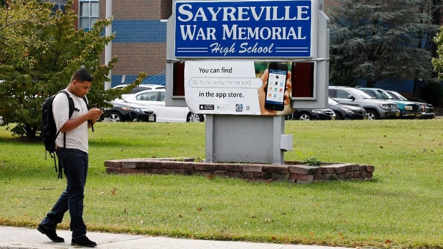 Sayreville War Memorial High School senior Kishan Patel, 17, walks past the entrance to the high school, Tuesday, Oct. 7, 2014, in Sayreville, N.J. Officials at a school, which has won three sectional titles over the past four years, canceled the football season amid allegations of harassment, intimidation and bullying among players. (AP Photo/Mel Evans)