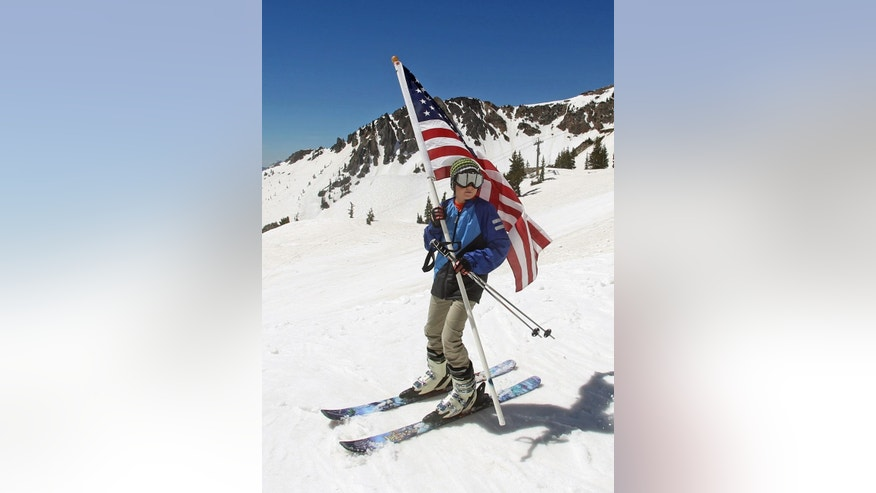 FILE - In this May 26, 2014, file photo, Carter Budge, 11, of Sandy, Utah, skis with a flag during the Snowbird Ski Resort's final day of skiing and riding for the 2013/14 winter season, in Little Cottonwood Canyon in the Wasatch Range, outside of Salt Lake City. In a lawsuit announced Wednesday, Oct. 8, 2014, Steamboat Ski and Resort Corp. in Steamboat Springs, Colo. says Salt Lake City can't market itself as Ski City USA because the winter sports title is already taken. (AP Photo/Rick Bowmer, File)