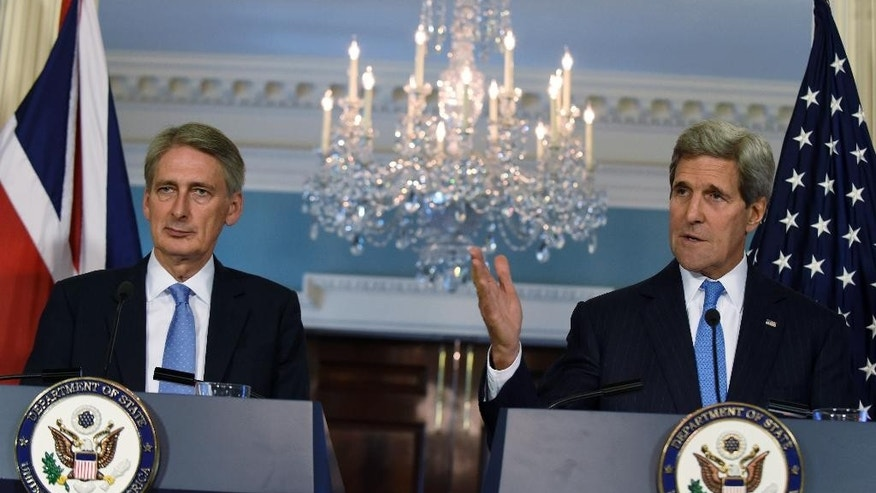 Secretary of State John Kerry, accompanied by British Foreign Secretary Phillip Hammond speaks during a media availability at the State Department in Washington, Wednesday, Oct. 8, 2014. (AP Photo/Susan Walsh)