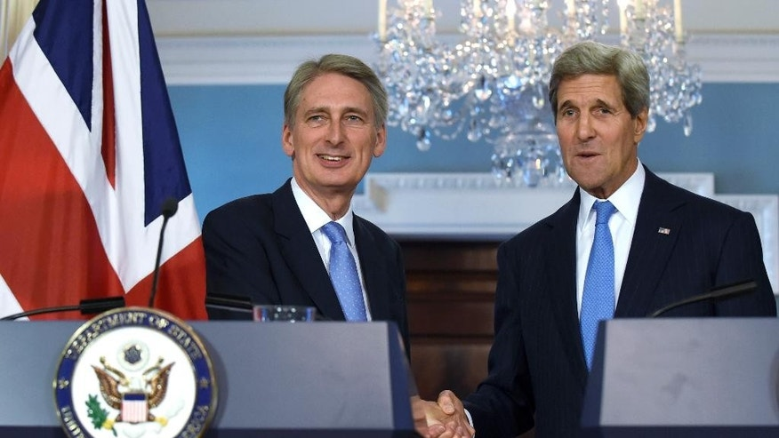 Secretary of State John Kerry and British Foreign Secretary Phillip Hammond shake hands following a media availability at State Department in Washington, Wednesday, Oct. 8, 2014. (AP Photo/Susan Walsh)