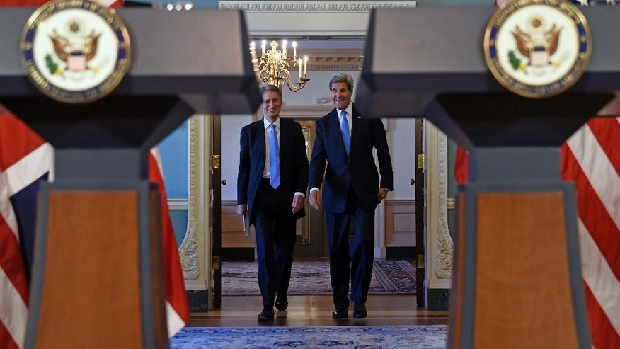 Secretary of State John Kerry and British Foreign Secretary Phillip Hammond arrive for a media availability at State Department in Washington, Wednesday, Oct. 8, 2014. (AP Photo/Susan Walsh)
