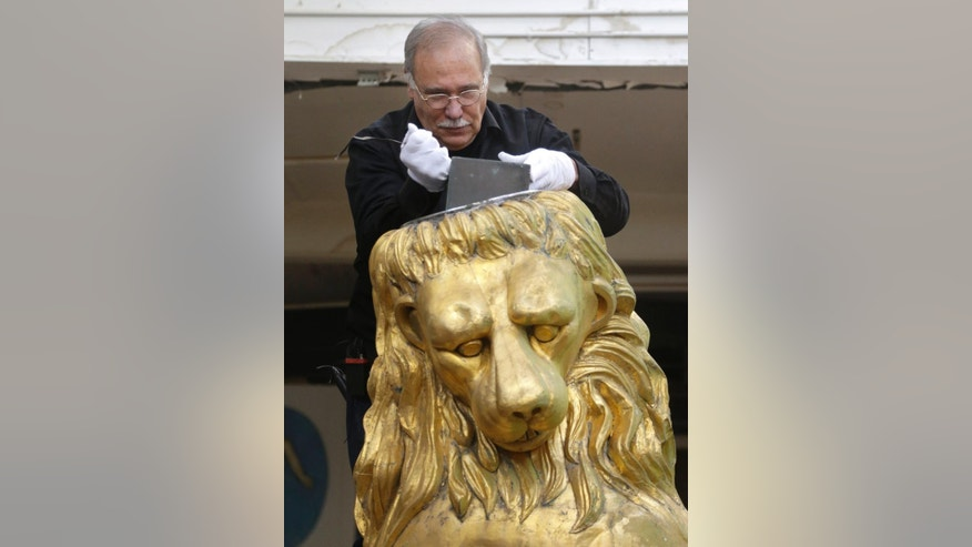 Sculptor and art restorer Robert Shure removes a copper box from a lion statue at a studio, Thursday, Oct. 9, 2014 in Woburn, Mass. Historians and restorers removed and opened a small copper box that has been hidden for more than a century inside the statue, which has been sitting atop Boston's Old State House until it was taken down for refurbishing.  Discovered inside the box were a hardcover book, along with papers from 1901, when the time capsule was sealed. Nothing was taken out of the box because of the items' fragile condition.  (AP Photo/Steven Senne)