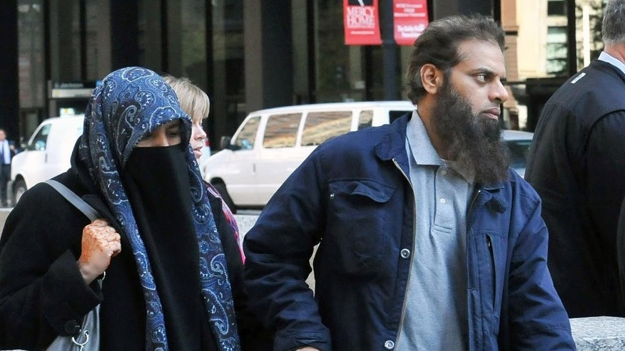 The parents of Mohammed Hamzah Khan, a 19-year-old U.S. citizen from Bolingbrook, Ill., leave the Dirksen federal building Monday, Oct. 6, 2014 in Chicago. Their son, Mohammed Hamzah Khan, was was arrested Saturday at O'Hare International Airport, from where he intended to travel to Turkey so that he could sneak into Syria to join the Islamic State group, according to criminal complaint released Monday. Khan is charged with attempting to provide material support to a foreign terrorist organization. A federal judge has ordered him held until a detention hearing Thursday. (AP Photo/Sun-Times Media, Al Podgorski)  MANDATORY CREDIT, MAGS OUT, NO SALES