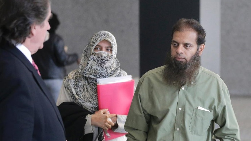 The parents of Mohammed Hamzah Khan meet with the family's attorney Thomas Dirkin, left, before Khan's detention hearing in federal court in Chicago on Thursday, Oct. 9, 2014. The 19-year-old suburban man, accused of seeking to travel to Syria to join Islamic State militants, is charged with attempting to provide material support to foreign terrorists. (AP Photo/Charles Rex Arbogast)