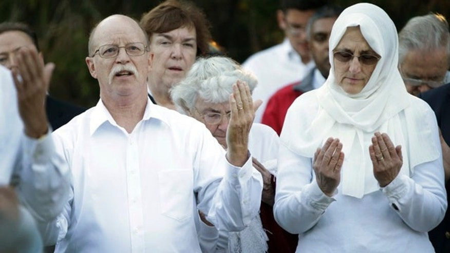 October 8, 2014: Ed Kassig, left, and wife Paula pray during a vigil for their son Abdul-Rahman Kassig, who last week was named the next beheading target of the Islamic State terror group, at Butler University in Indianapolis. (AP Photo/AJ Mast)