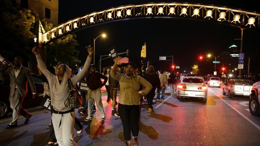 Protesters march down a street blocking traffic Thursday, Oct. 9, 2014, a day after Vonderrit D. Myers was shot and killed by white, off-duty St. Louis police officer in St. Louis. Police say Myers was shot Wednesday after he opened fire on the off-duty officer, but Myers' parents say he was unarmed.(AP Photo/Jeff Roberson)