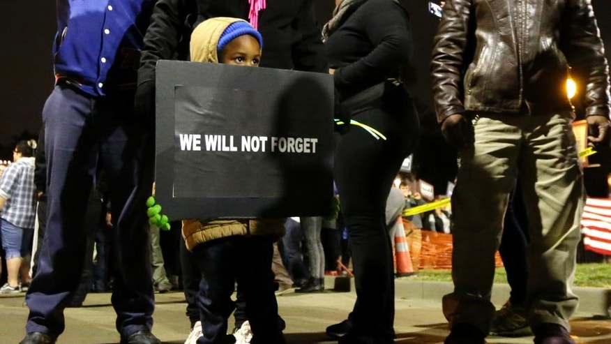 A young boy joins protesters as they gather across the street from the Ferguson, Mo., police station, in a continuing protest of the shooting of Michael Brown, Friday, Oct. 10, 2014, in Ferguson, Mo. (AP Photo/Charles Rex Arbogast)