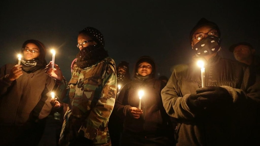 Young women attend a candlelight vigil for victims of gun violence Friday, Oct. 10, 2014, in Ferguson, Mo. (AP Photo/Charles Rex Arbogast)