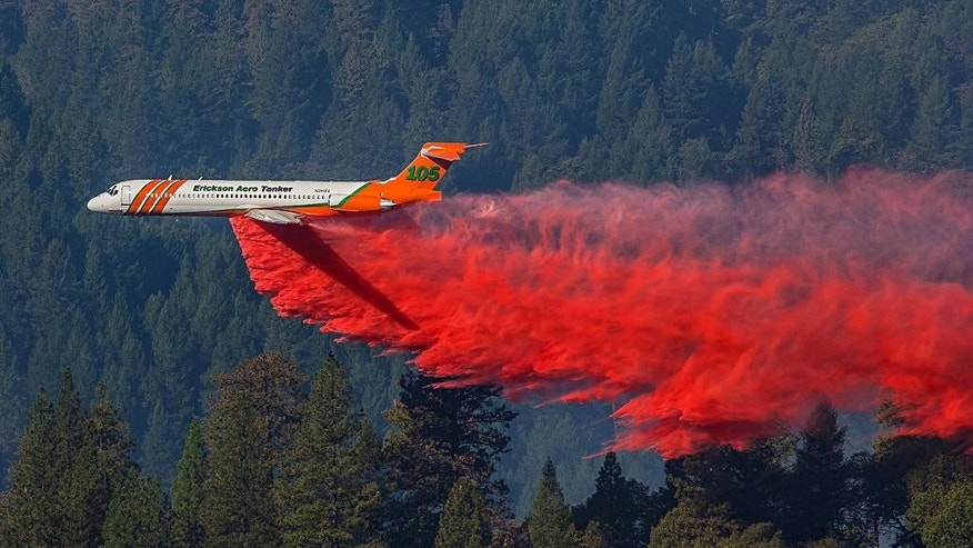 This Thursday, Oct. 9, 2014 photo, a firefighting aircraft drops retardant over a wildfire along a hillside near Foresthill, Calif.  Fire crews are making steady progress against a wildfire burning near a Northern California interstate that has destroyed six homes and is threatening hundreds more. State fire officials say the blaze along Interstate 80 about 40 miles northeast of Sacramento was holding steady at 420 acres on Friday while containment increased to 30 percent. (AP Photo/ Tony Hallas)