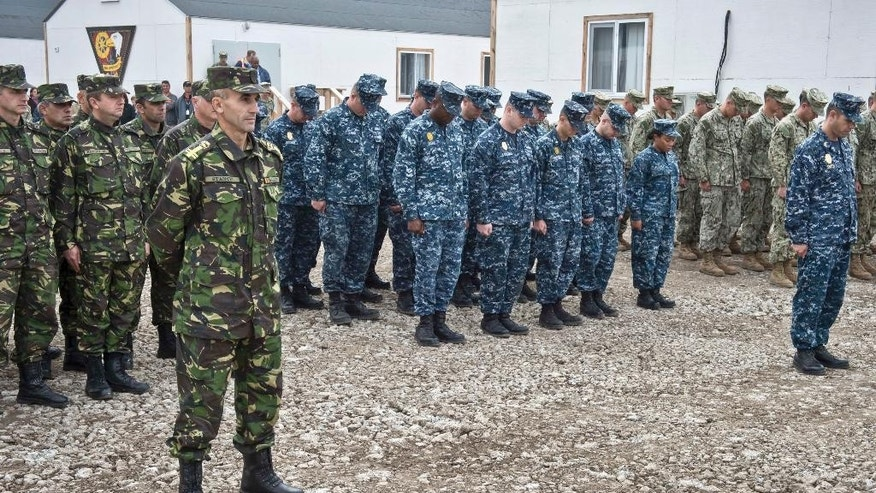 In this handout photograph from the US Navy, US service members deployed to the Naval Support Facility (NSF) Deveselu, groups center and right, bow their heads with members of the Romanian Military, left, during a religious moment of the establishment and assumption of command ceremony in Deveselu, Romania, Friday, Oct. 10, 2014. The NSF Deveselu Base, established more than 20 years ago, will be part of the Aegis Ballistic Missile Defense (BMD) System. The US Navy has taken control of a new missile defense base in southern Romania, one of two European land-based interceptor sites for a NATO missile shield which Russia strongly opposes.(AP Photo/U.S. Navy / LT j.g. Alexander Perrien, Handout)