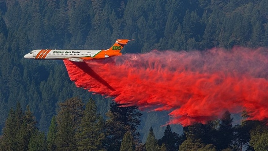 October 9, 2014: A firefighting aircraft drops retardant over a wildfire along a hillside near Foresthill, Calif.  (AP Photo/ Tony Hallas)