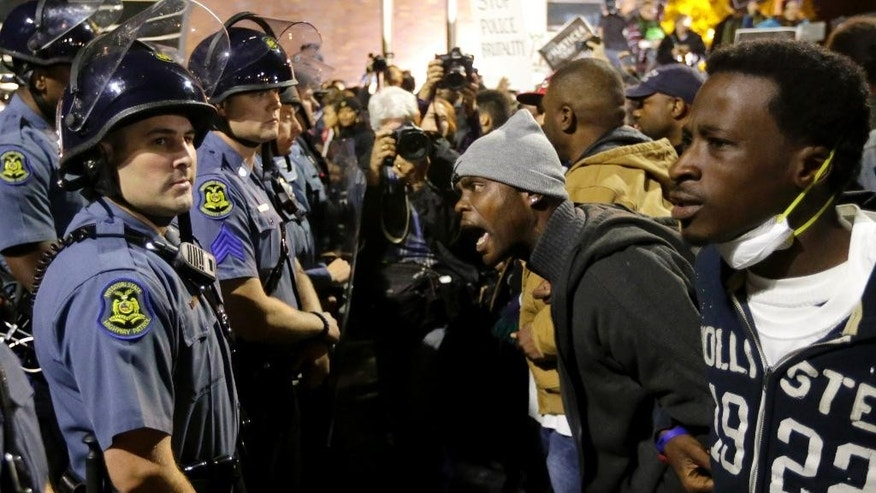 A protester yells at a Missouri State Police officer during a protest at the Ferguson, Mo., police headquarters Friday, Oct. 10, 2014, in Ferguson.  (AP Photo/Charles Rex Arbogast)