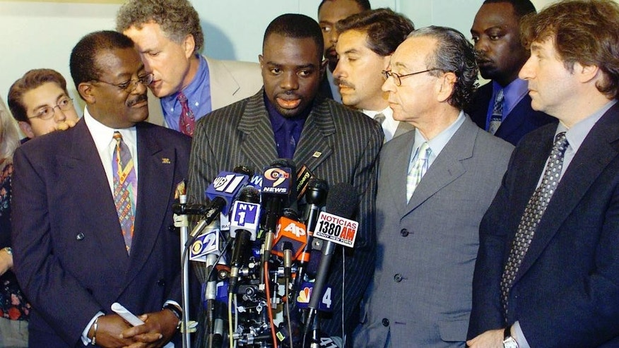 FILE - In this July 12, 2001, file photo, Abner Louima, second from left, stands with his attorneys Johnnie Cochran, far left, Peter Neufeld, to the right of Louima, Sanford Rubenstein, second from right, and Barry Scheck, far right, while speaking during a news conference in New York. Rubenstein is focused on a new police investigation,  a potential rape suspect. In a turn that's whiplash-inducing even for a city where the outlandish is ordinary, the suddenly scarce Rubenstein is under scrutiny from the police force he's lambasted for years as he built a flamboyant persona and a fortune. (AP Photo/Beth A. Keiser, File)