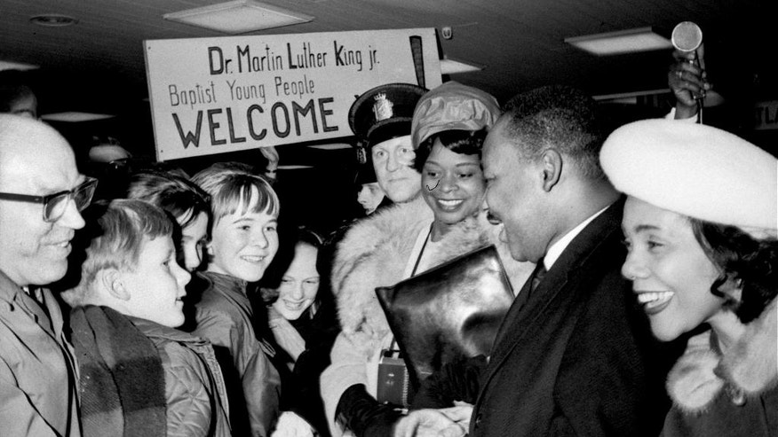 In this Dec. 8, 1964, file photo, U.S. civil rights leader Dr. Martin Luther King, Jr. is welcomed by Baptist youths on his arrival in Oslo, Norway. Dr. King is flanked by his wife, Coretta, right, and his secretary, Miss Dora McDonald. Dr. King is in the Norwegian capital to accept the 1964 Nobel Peace Prize to be presented to him during ceremonies on December 10. (AP Photo, File)