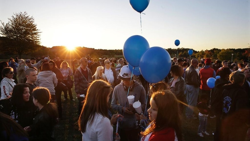 Hundreds of people gather in the setting sun, for an anti-bullying rally Sunday, Oct. 12, 2014, in Sayreville, N.J. The central New Jersey town that's been rocked by allegations of hazing on its football team that prompted the cancellation of the rest of the season. Organizers say the goal of the event is to promote unity and healing within the community, as well as to show support for the victims of bullying. (AP Photo/Mel Evans)