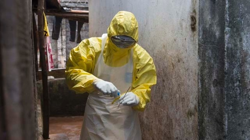 Oct. 6: A health worker in protective equipment prepares a sample taken from the body of someone who is suspected to have died from Ebola virus, near Rokupa Hospital in Freetown.