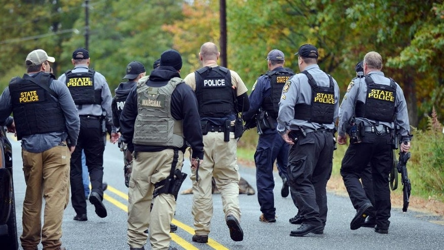 Police search an area in Price Townhsip Pa., near Alpine Ski Resort on Saturday, Oct. 11, 2014, as they look for Eric Frein, the suspect in last month's deadly ambush at a state police barracks. (AP Photo/The Times-Tribune, Jason Farmer)