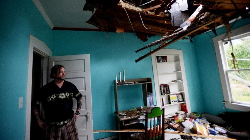 John Brooks looks into the room that was hit by a tree during the storm Monday, Oct. 13, 2014, in Monroe, La, it was going to be the nursery for his expected baby. (AP Photo/The Shreveport Times, Henrietta Wildsmith)