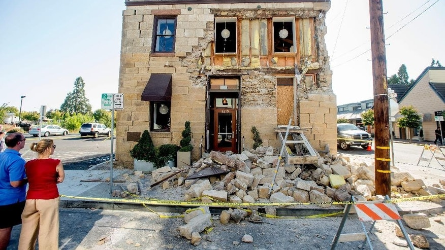 FILE - In this Aug. 24, 2014, file photo, pedestrians examine a crumbling facade following an earthquake at the Vintner's Collective tasting room in Napa, Calif. Four long fault segments running beneath northern California and its roughly 15 million people all have become locked far underground, and loaded with enough tension to produce earthquakes of magnitude 6.8 or greater, a geological study published Monday, Oct. 13, 2014 says. (AP Photo/Noah Berger, File)
