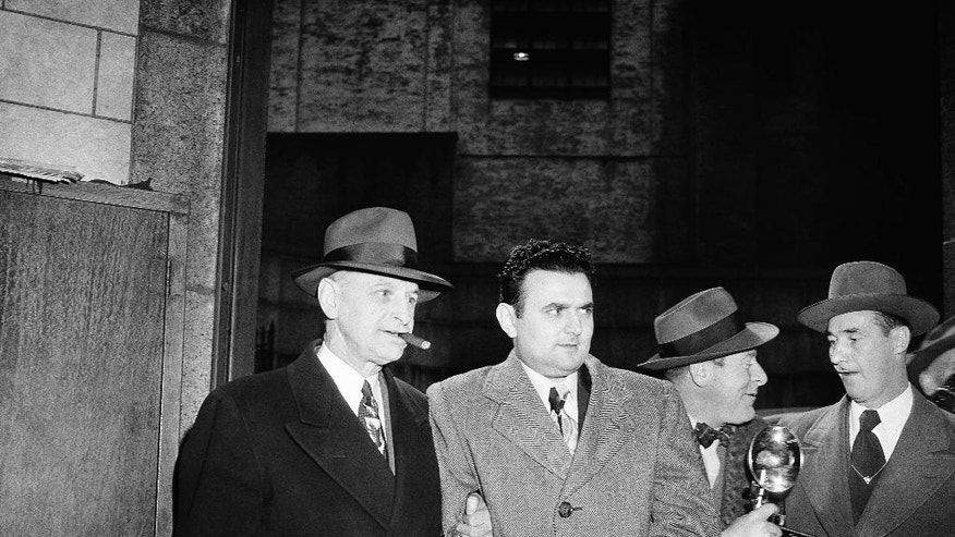 FILE - In this April 5, 1951, file photo, David Greenglass, second from left, former army sergeant, is led into Federal Courthouse in New York by U.S. Deputy Marshall Eugene Fitzgerald, left, for sentencing as an atom spy. Greenglass, whose testimony led to the conviction and execution of his sister, Ethel Rosenberg and brother-in-law, Julius Rosenberg, died on July 1. He was 92. (AP Photo/File)