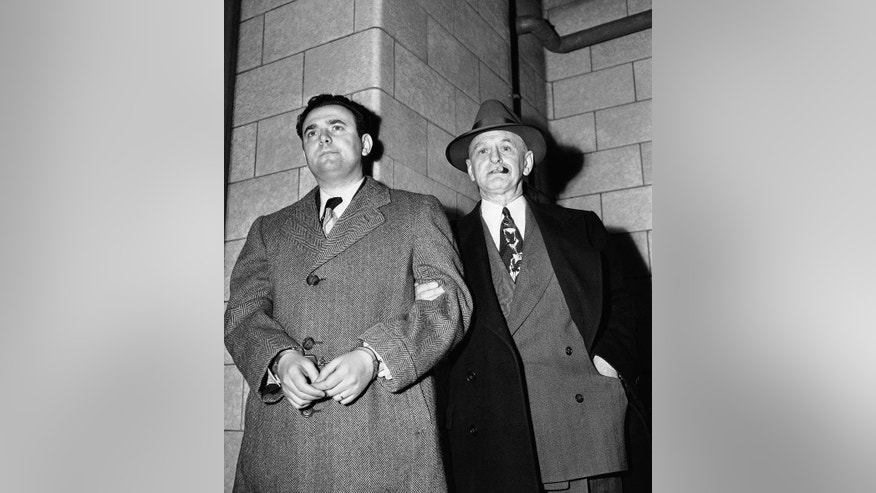 FILE - In this April 6, 1951, file photo, David Greenglass, left, arrives at Federal Court led by U.S. Deputy Marshal Eugene Fitzgerald in New York for sentencing as a member of an atomic spy ring which passed on secrets to Russia. Greenglass pleaded guilty. The former Army sergeant whose testimony led to the conviction and execution of his sister, Ethel Rosenberg and brother-in-law, Julius Rosenberg, died on July 1. He was 92. (AP Photo/File)