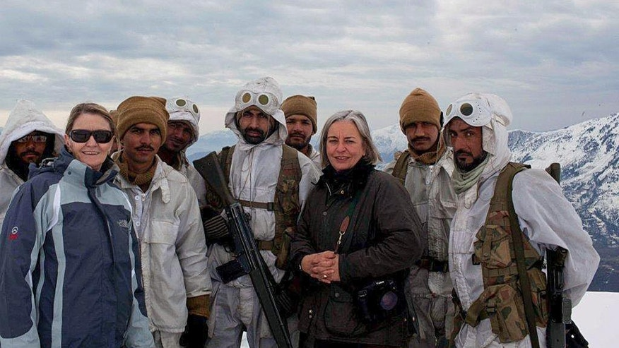 In this photo taken in February 2012, Associated Press reporter Kathy Gannon, front left, and photographer Anja Niedringhaus, third from right, pose for a photo with Pakistani soldiers while embedded with them in a remote mountain outpost in northwest Pakistan near the Afghan border. Gannon spoke Oct. 9, 2014, during her first interview since she and Niedringhaus were attacked on April 4, 2014, by a gunman in Khost Province in eastern Afghanistan as they prepared to cover the presidential election the next day. Niedringhaus was killed in the attack and Gannon is recovering from multiple gunshot wounds. (AP Photo)