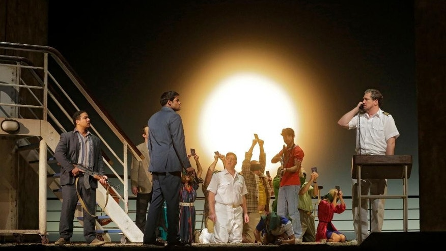 "In this image released by the Metropolitan Opera, Aubrey Allicock as Mamoud, foreground from left, Sean Pannikar as Molqui, and Paulo Szot as the Captain, perform with the cast  in ""The Death of Klinghoffer,""  at the Metropolitan Opera in New York. (AP Photo/Metropolitan Opera, Ken Howard)"