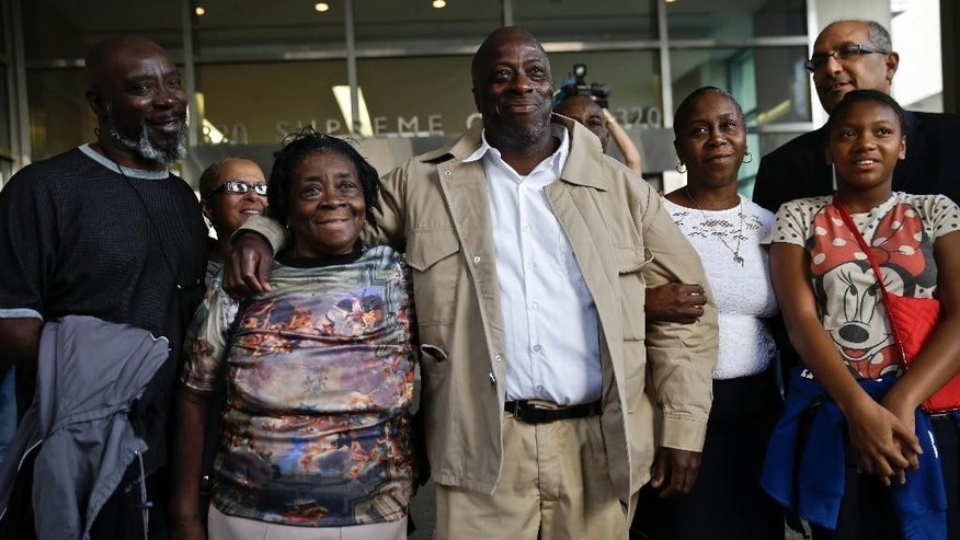 David McCallum, center, hugs his mother Ernestine McCallum as he stands with his immediate family outside Supreme Court on Wednesday Oct. 15, 2014 in New York.  A judge exonerated McCallum, and Wille Stuckey, who died in prison, of  wrongful imprisonment for murder after nearly 30 years.  (AP Photo/Seth Wenig)