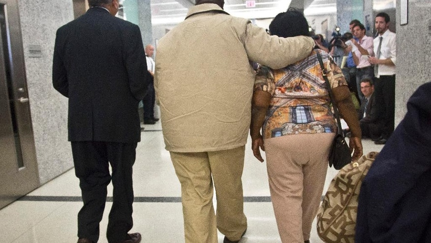 David McCallum, center, walks with his mother Ernestine McCallum and lawyer Oscar Michelen, left, to a news conference after his exoneration Wednesday, Oct. 15, 2014, in New York. McCallum and Willie Stuckey, who died in prison, were 16 years old when they were convicted of murder. A judge exonerated both men for wrongful conviction. (AP Photo/Bebeto Matthews)