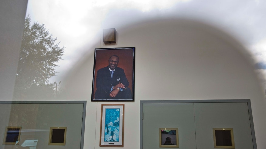 Oct. 14, 2014: The sun and clouds are reflected off a glass on the entrance of the Shiloh Missionary Baptist Church where a portrait of pastor Juan D. McFarland hangs on the wall in Montgomery, Ala. (AP/Brynn Anderson)