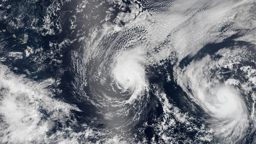 FILE - This Aug. 5, 2014 file satellite image provided by NASA shows two tropical Pacific Ocean hurricanes - Iselle at center and Julio at right - bearing down on Hawaii, top left. Residents on Hawaii's southernmost island have already dealt with one tropical storm this year and are currently coping with the threat of slowly encroaching lava. Now, meteorologists say a potential hurricane is heading toward them and the rest of the island chain. The governor on Wednesday, Oct. 15, 2014, proclaimed an emergency to help the state respond to the storm. (AP Photo/NASA, File)