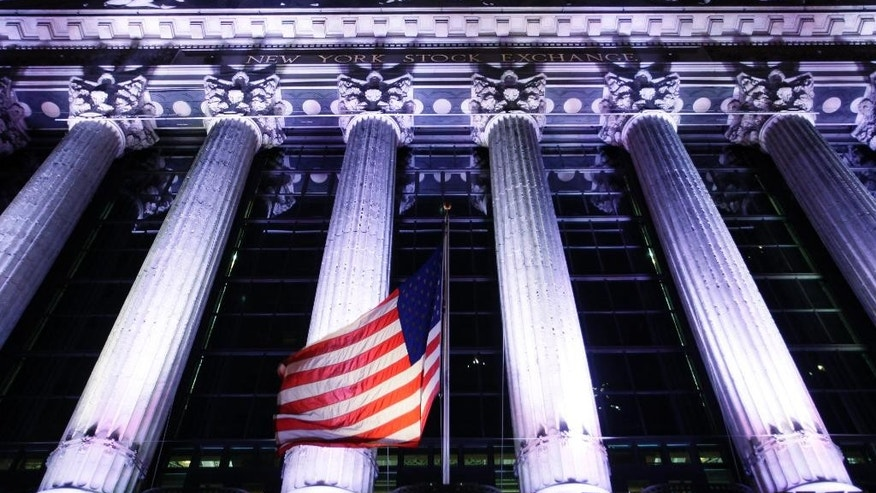 In this Oct. 8, 2014 photo, an American flag flies in front of the New York Stock Exchange in New York. U.S. stocks are plunging in early trading Wednesday, Oct. 15, 2014, as traders flee risky assets. (AP Photo/Mark Lennihan)