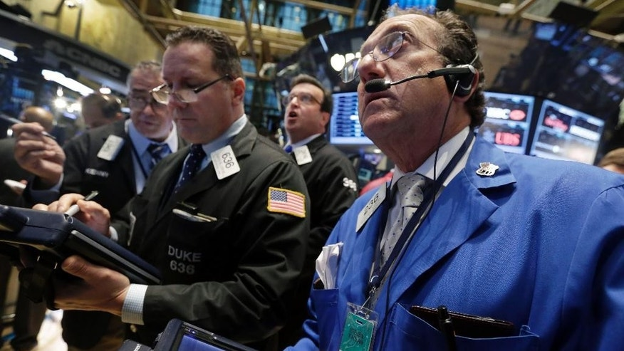 Traders gather at a post on the floor of the New York Stock Exchange Thursday, Oct. 16, 2014. U.S. stocks are opening lower while European markets suffer even steeper declines. (AP Photo/Richard Drew)