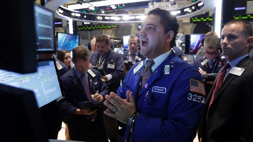 Specialist Ronnie Howard, center, calls out prices as he works at his post on the floor of the New York Stock Exchange Thursday, Oct. 16, 2014. Beyond the turmoil shaking financial markets, the U.S. economy remains sturdier than many seem to fear.  (AP Photo/Richard Drew)